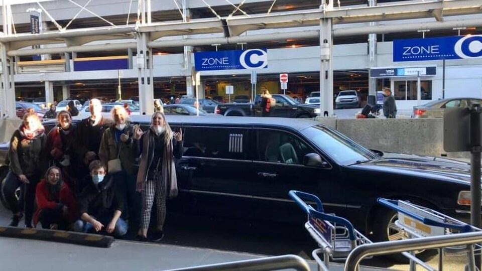 Un groupe d'étudiants devant une limousine