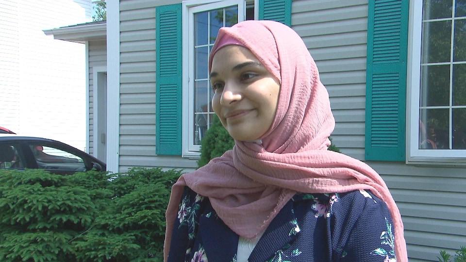 Une adolescente devant une maison.