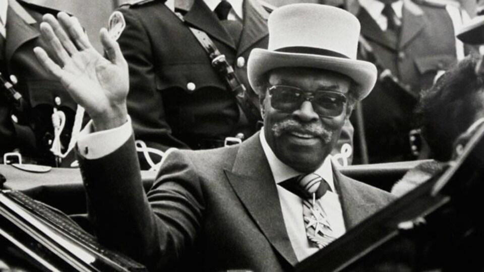 Le portrait d'un homme qui porte un chapeau et des lunettes dans une voiture
