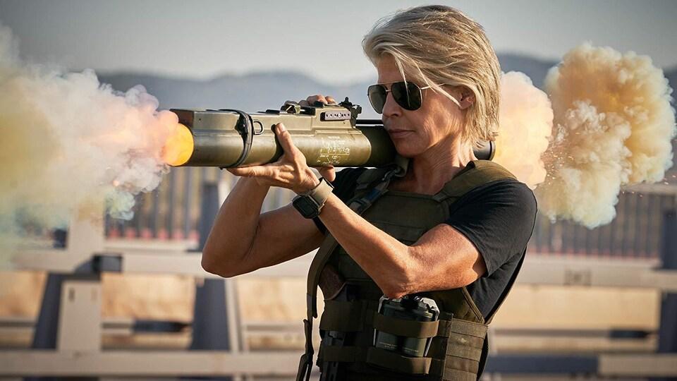 L'actrice Linda Hamilton dans son rôle de Sarah Connor dans le film « Terminator: Dark Fate », vêtue d'une veste pare-balles et tirant avec un lance-roquettes.