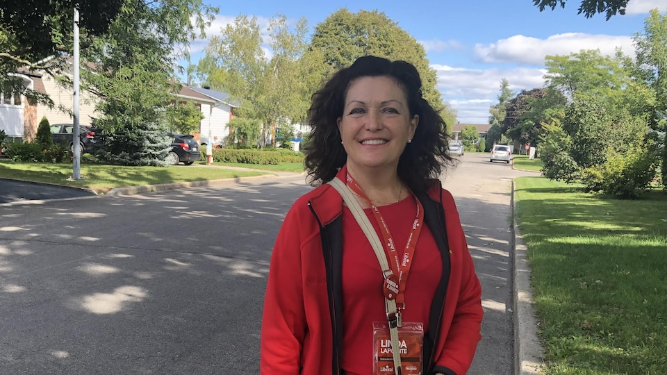 Linda Lapointe debout dans une rue résidentielle.