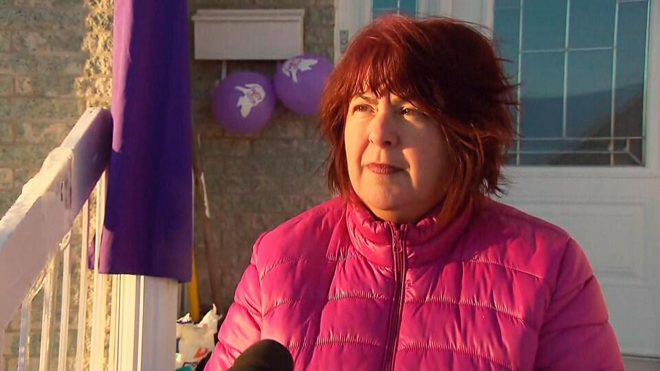 Une femme avec un manteau rouge, parle devant un micro. Elle est à l'extérieur devant une maison