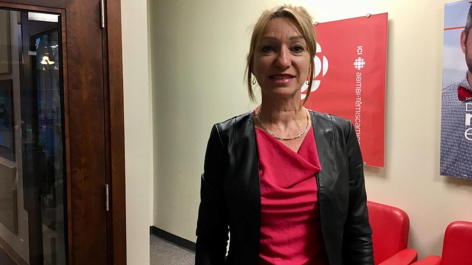 Linda Turcotte pose devant l'affiche de Radio-Canada Abitibi-Témiscamingue,