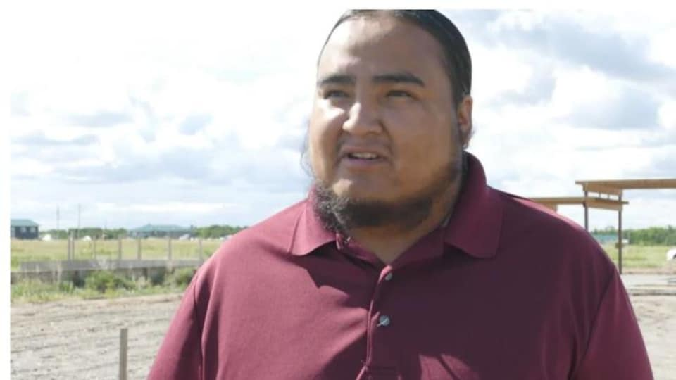 Lindsay Bunn, un homme de la Première Nation Birdtail Sioux, pose devant une structure de bois dans un espace rural.