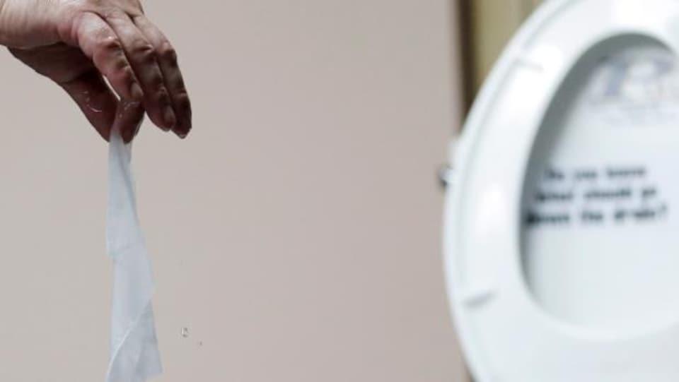 Une main tient une lingette humide devant la cuvette d'une toilette.