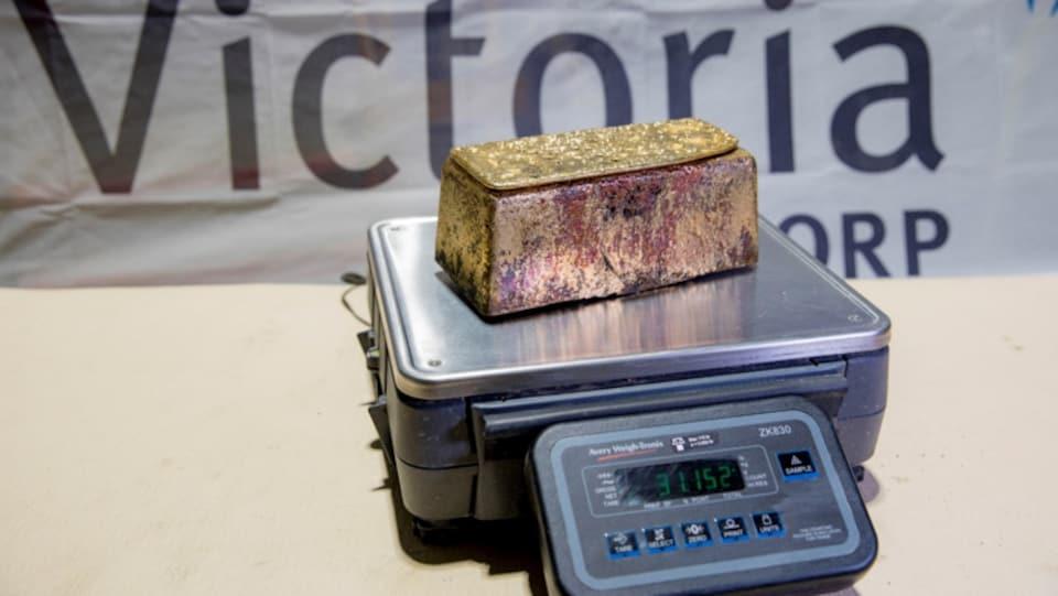 Le lingot d'or est posé sur une balance métallique.