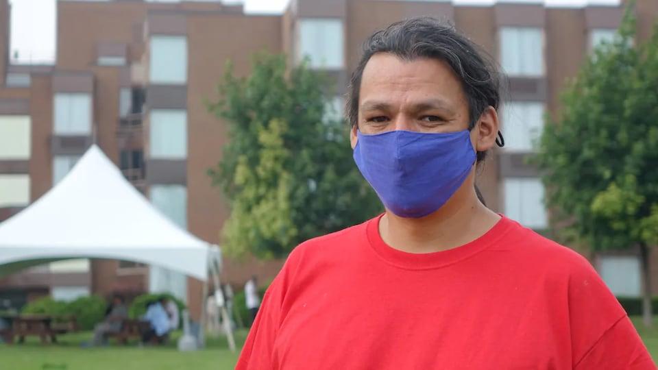 L'homme pose devant un immeuble de plusieurs étages, avec un masque de tissu bleu au visage.
