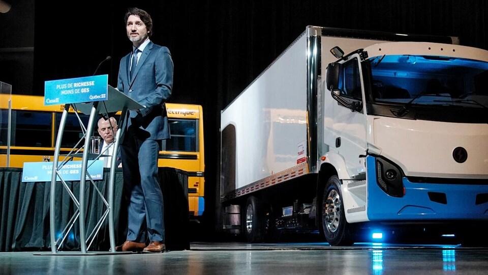 Justin Trudeau debout derrière un lutrin et devant un camion électrique.