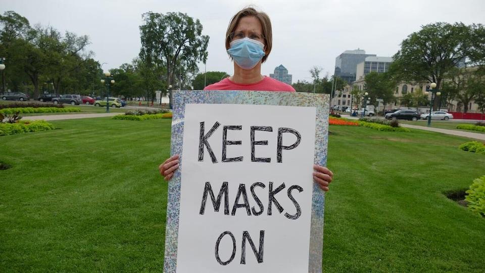 Lisa Bryski tenant une pancarte sur une pelouse.
