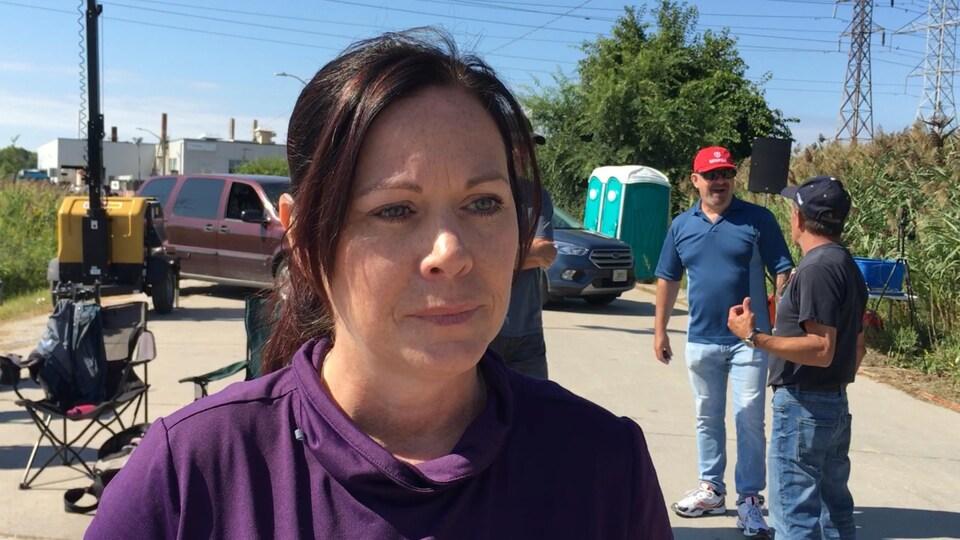 Une femme devant quelques manifestants.