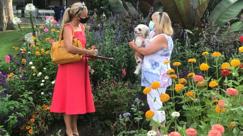 Lisa Robinson écoute une électrice dans un parc fleuri.