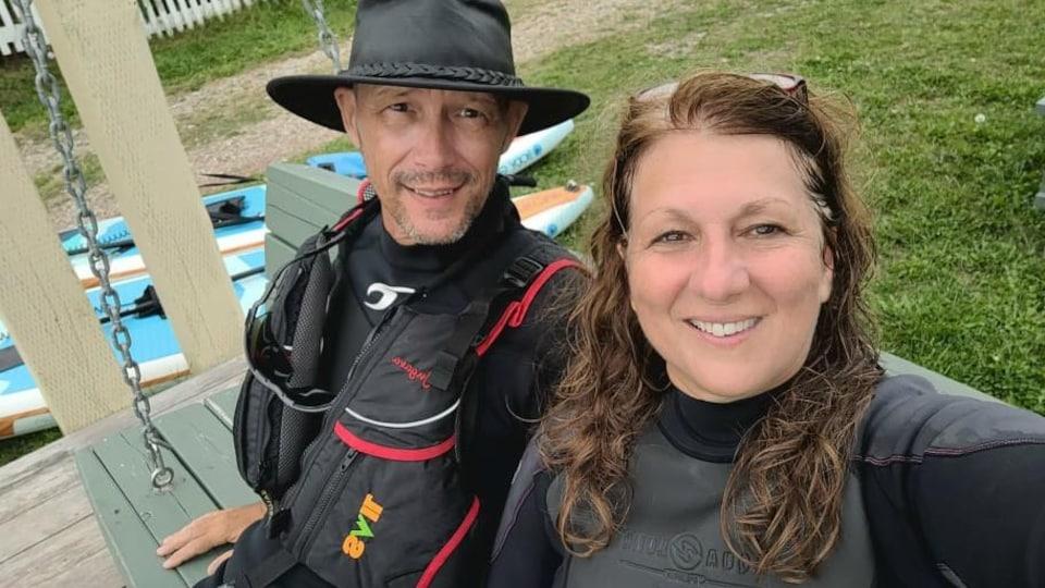 Normand Lambert et Lise Côté sont assis sur un banc. Ils sont vêtus de combinaisons de sports nautiques et des planches à pagaie sont sur le sol, près d'eux.