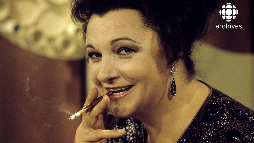 Plan rapproché de l'animatrice Lise Payette qui tient un fume-cigarette contenant une cigarette allumée entre ses lèvres.