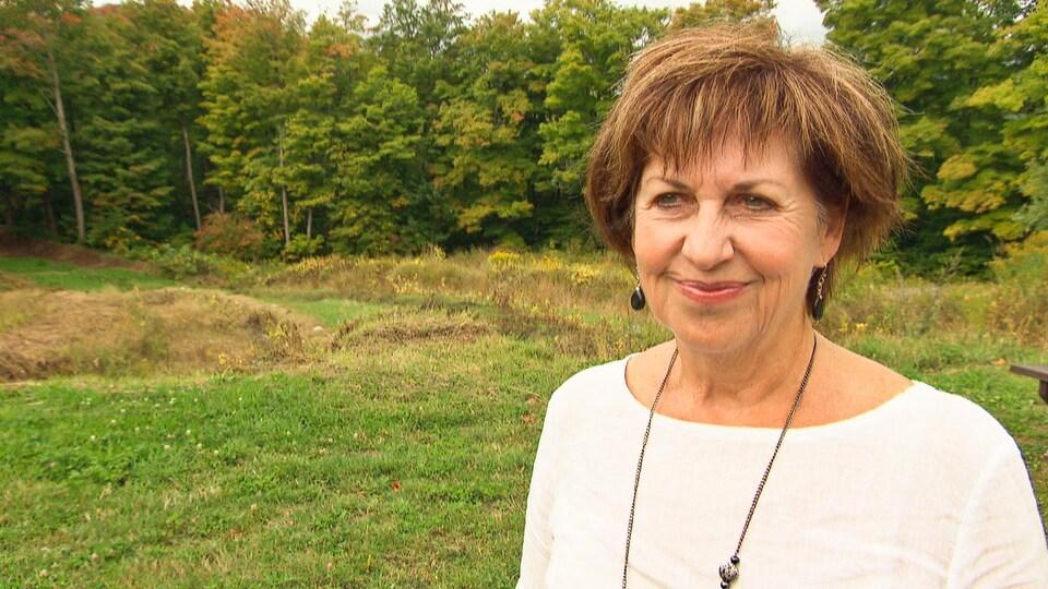 Lise Villeneuve en entrevue devant une forêt.