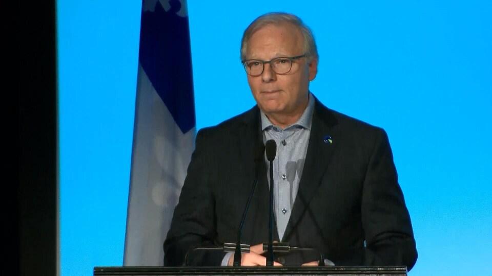 Jean-François Lisée se tient au lutrin avec un drapeau du Québec derrière lui.