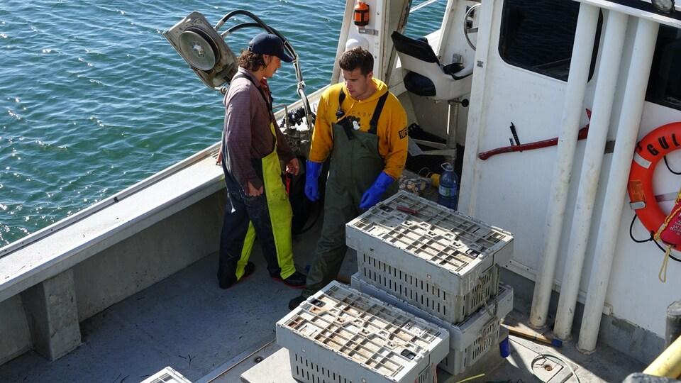 Deux pêcheurs à bord d'un bateau.