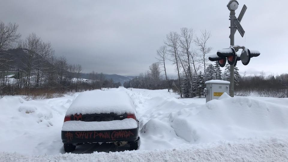 Une voiture enneigée bloque la voie ferrée. À l'arrière du véhicule, on peut lire « shut down Canada » écrit à la main.