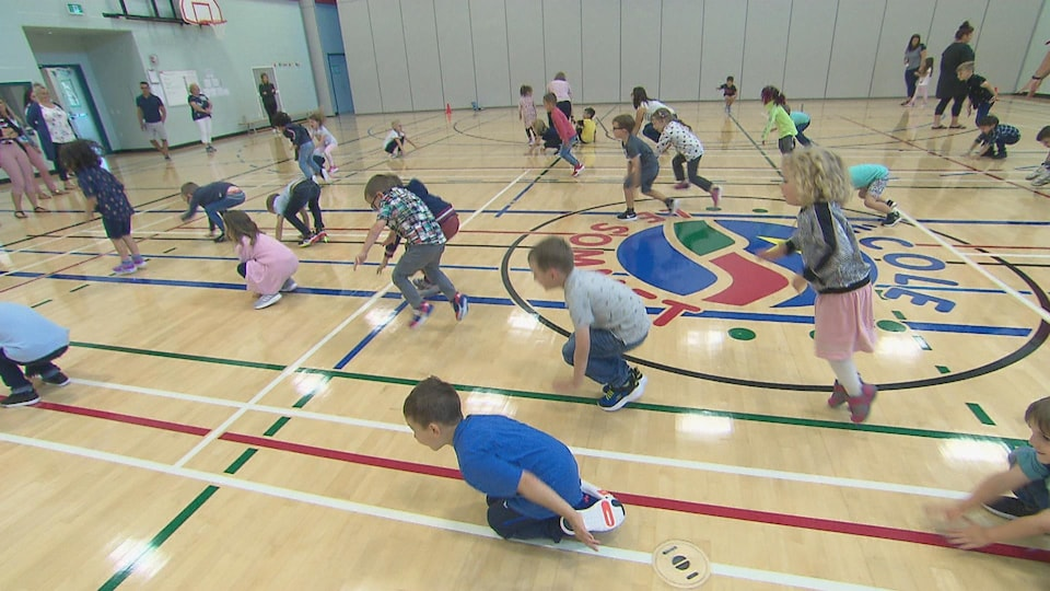 Des enfants qui font des exercices d'échauffement dans un gymnase.