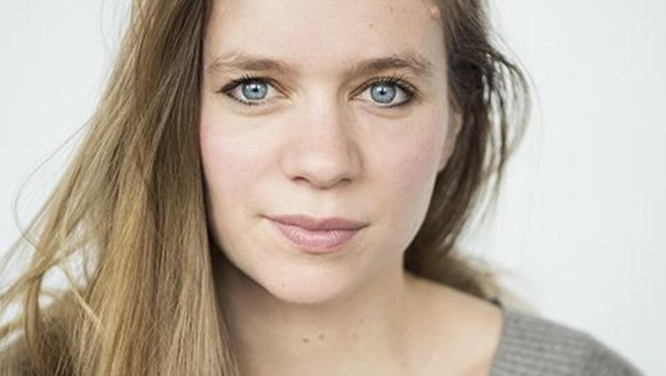 La jeune femme blonde aux yeux bleus regarde la caméra.