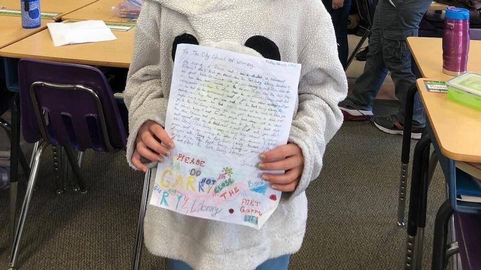 Une élève tient une lettre dans sa classe.