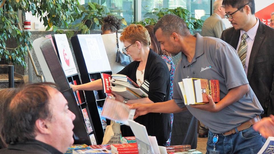 un homme prend un livre sur un étal, alors qu'il a déjà son autre main plein d'ouvrages. Derrière lui, des personnes regardent les livres présentés par les éditeurs, sur leurs stands.