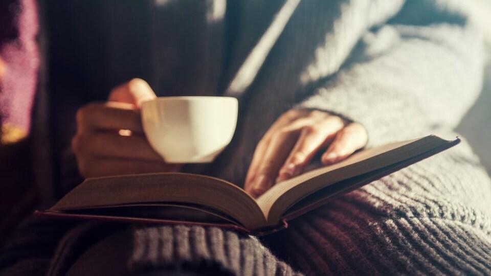 Une femme lit un livre en tenant une tasse de café.