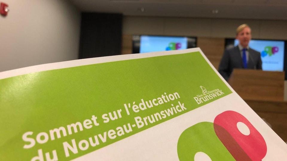 La brochure intitulée « Sommet sur l'éducation du Nouveau-Brunswick » et le ministre Cardy dans le fond de la salle.