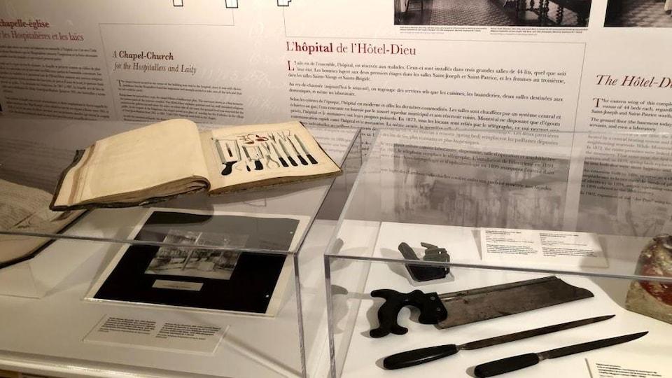 Des objets utilisés en médecine ancienne exposés près d'un livre montrant des dessins d'une partie de ces objets.