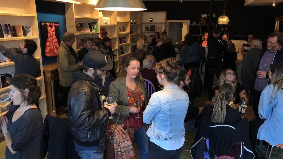 Des gens discutent en tenant des coupes de vin dans une librairie.
