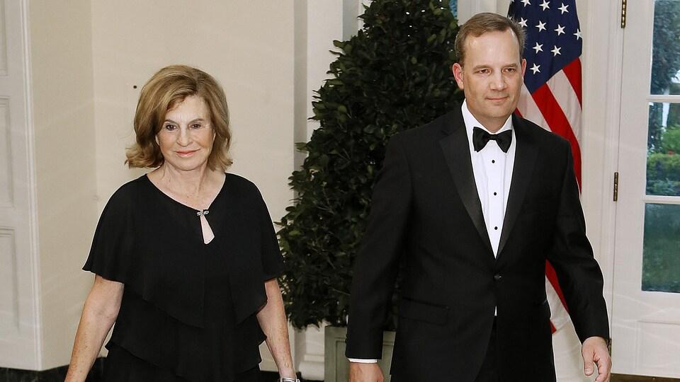 Une femme et un homme marchent à la Maison-Blanche.