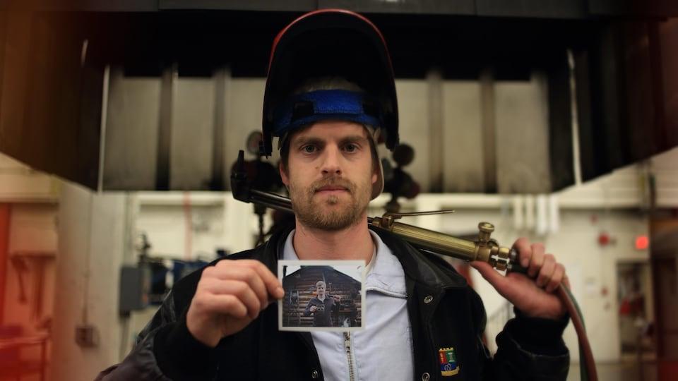 Lliam Hildebrand pose devant la caméra. Il tient une photo dans sa main.