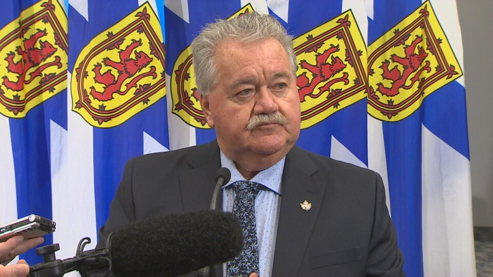 Lloyd Hines répond aux questions des médias devant des drapeaux de la Nouvelle-Écosse le 10 janvier 2019.