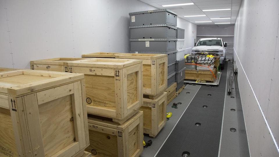 Intérieur avec des caisses en bois, une voiture et des boîtes en métal.