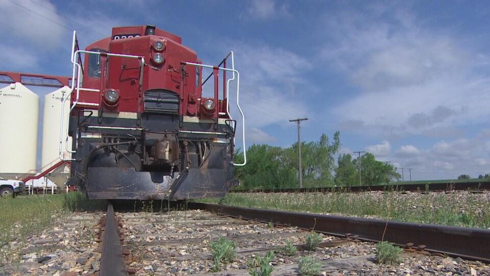 Une locomotive rouge, vue de devant, stationnée sur la voie ferrée.