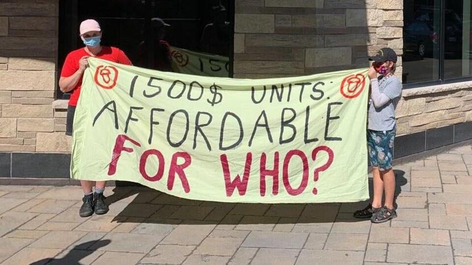 Des manifestants tiennent une bannière sur laquelle on lit « Des appartements à 1500 $ : abordables pour qui? ».