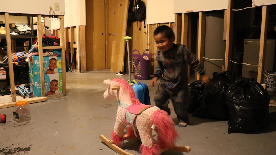 Un enfant joue devant un cheval rose et des sacs de poubelles et des paquets de couches.