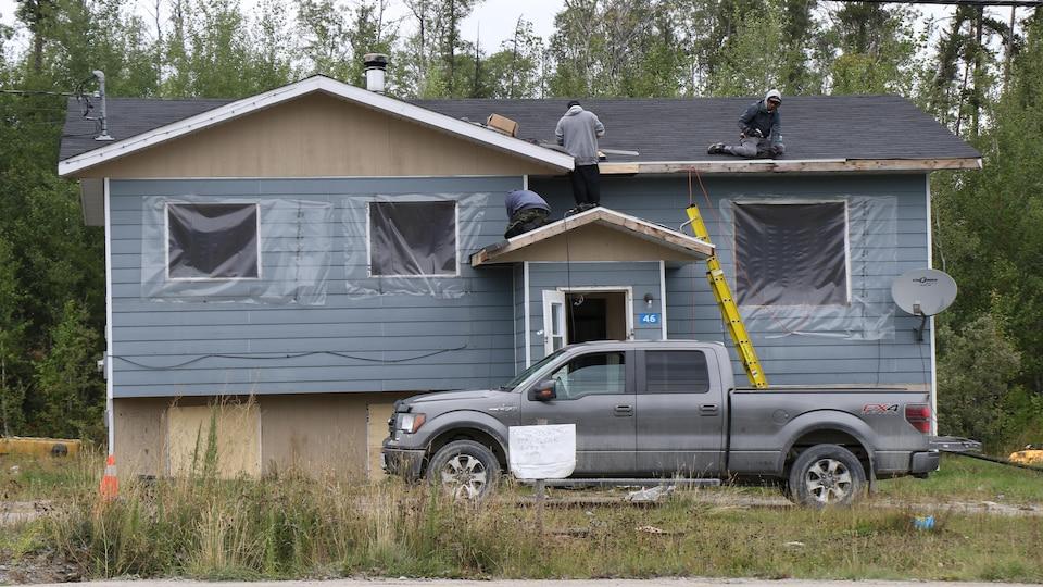 Des ouvriers s'affairent à réparer le toit d'une maison dans une communauté autochtone de l'Ontario.