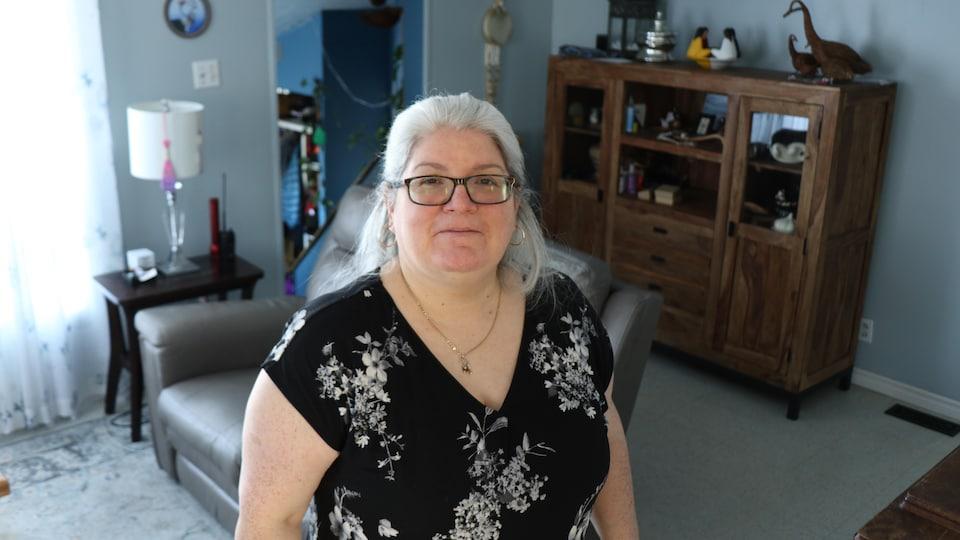 Une femme pause au milieu de son salon.