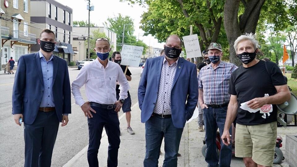 Les hommes portent des masques où l'on peut lire : pour le droit au logement!