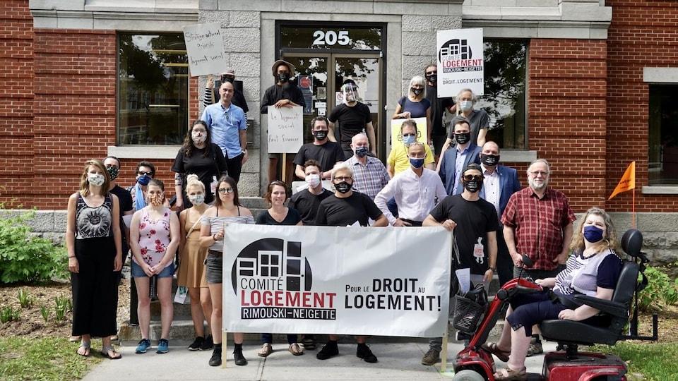 Des manifestants tiennent une banderole où l'on peut lire : pour le droit au logement!