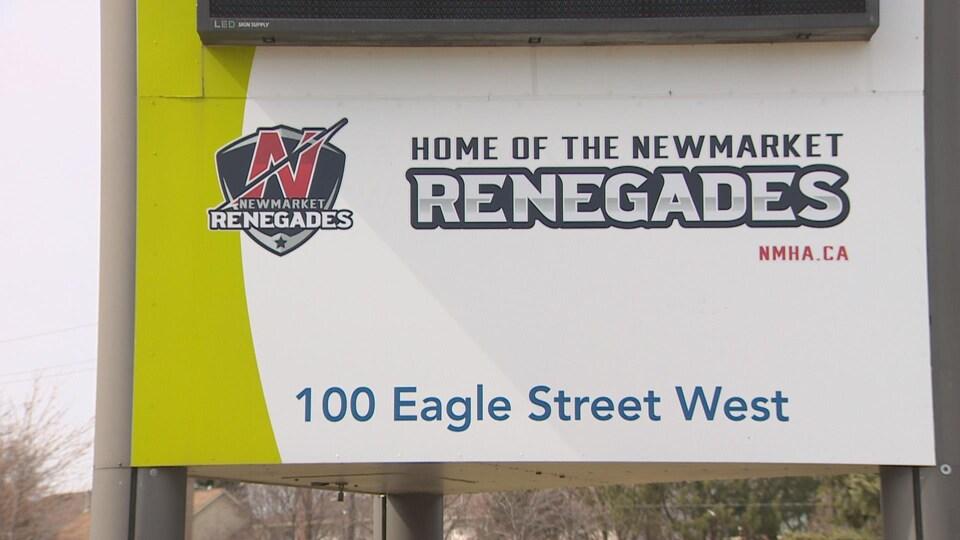 Une enseigne sur laquelle figure le nouveau logo de l'Association de hockey mineur de Newmarket, soit un bouclier sur lequel un « N » est traversé par un éclair. À droite de l'image, il est inscrit « Home of the Newmarket Renegades ».