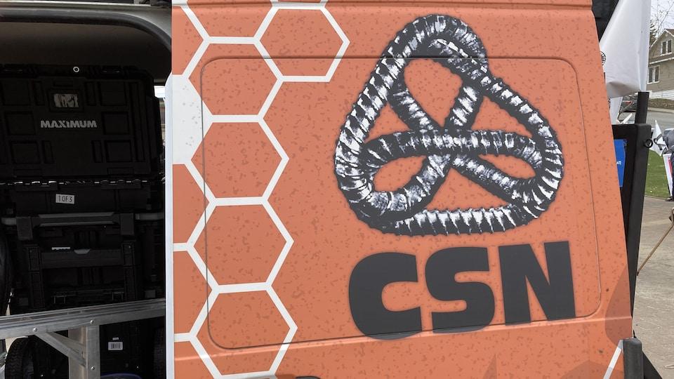 Le logo de la CSN sur la porte d'un véhicule.