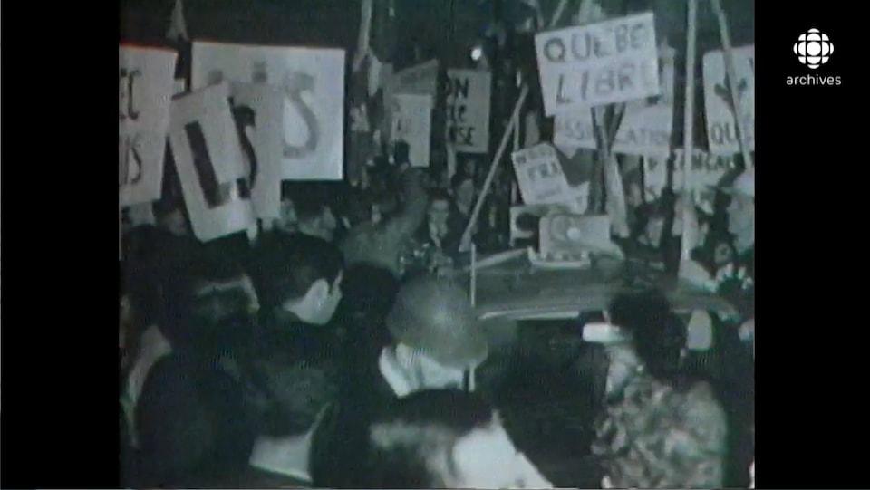 Masse de manifestants avec des pancartes, dont une avec le message «Québec libre».