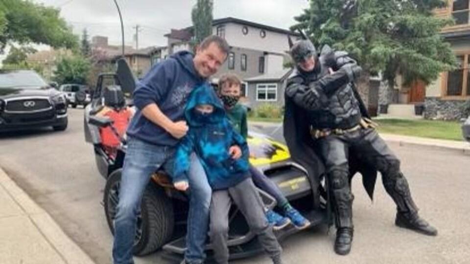 Les deux frères Germaine en compagnie de leur père et d'un homme habillé en costume de Batman devant une voiture transformée en Batmobile.