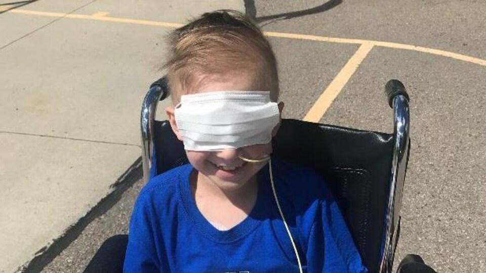 Un garçon assis dans un fauteuil roulant. Il porte un masque sur les yeux.