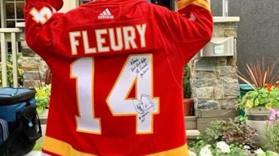 Un garçon porte un chandail de hockey signé par le joueur de Theoren Fleury.