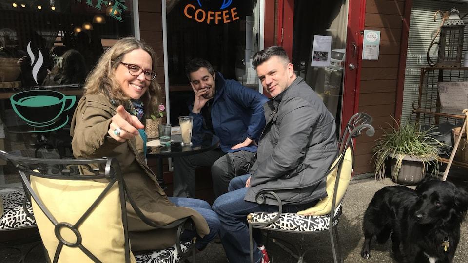 Trois personnes assises à la table d'un café, à l'extérieur, avec un chien noir juste à côté.