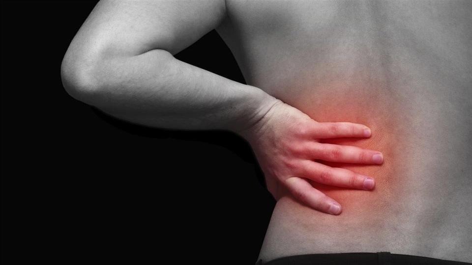 Une personne a mal au bas du dos.
