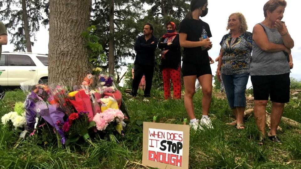 """Des bouquets de fleurs déposés sur le gazon près d'un arbre où se trouve également un panneau sur lequel il est inscrit en anglais """"Quand est-ce que cela va s'arrêter. C'est assez"""". Cinq personnes se trouvent sur place."""