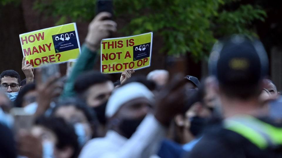 Des participants brandissent des pancartes réclamant des gestes concrets pour que des événements semblables ne se reproduisent pas.